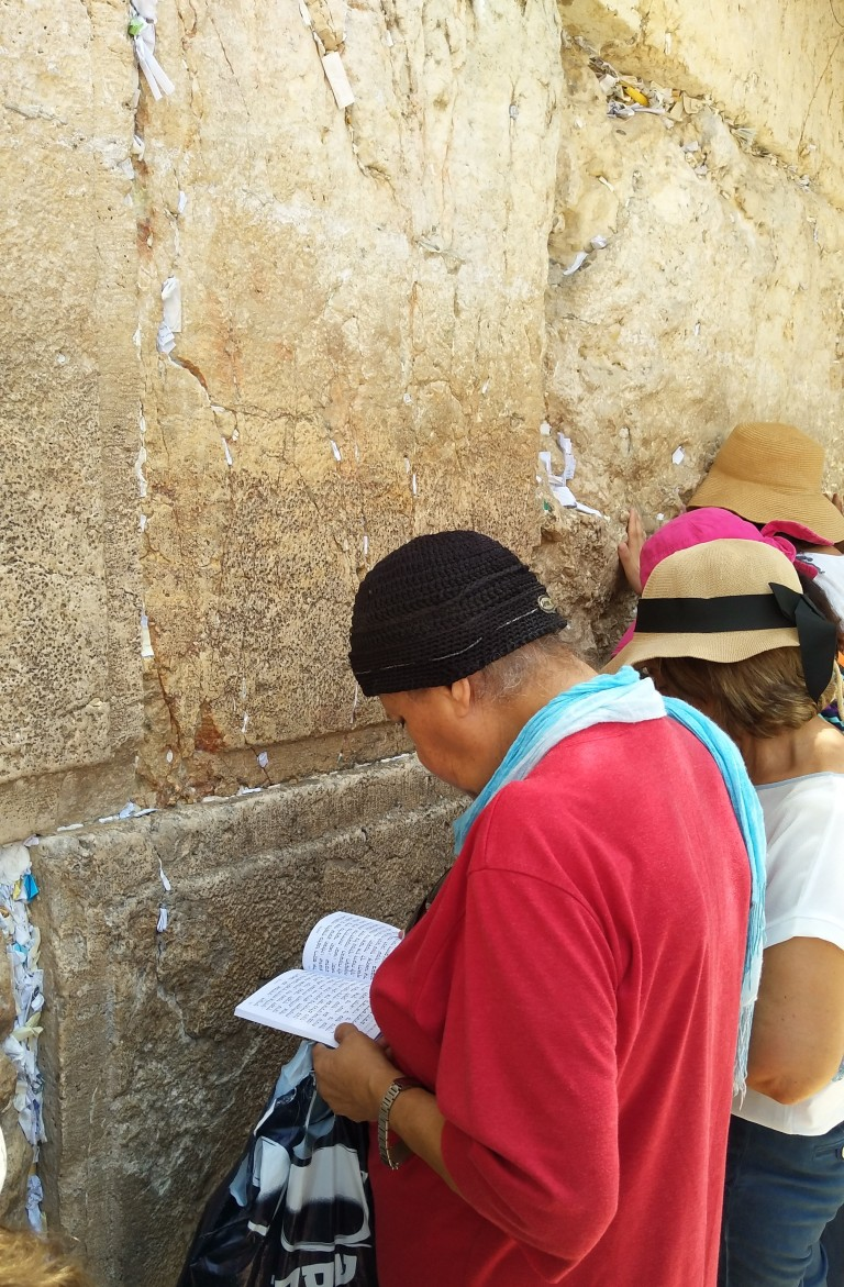Woman praying at the Western wall in Israel